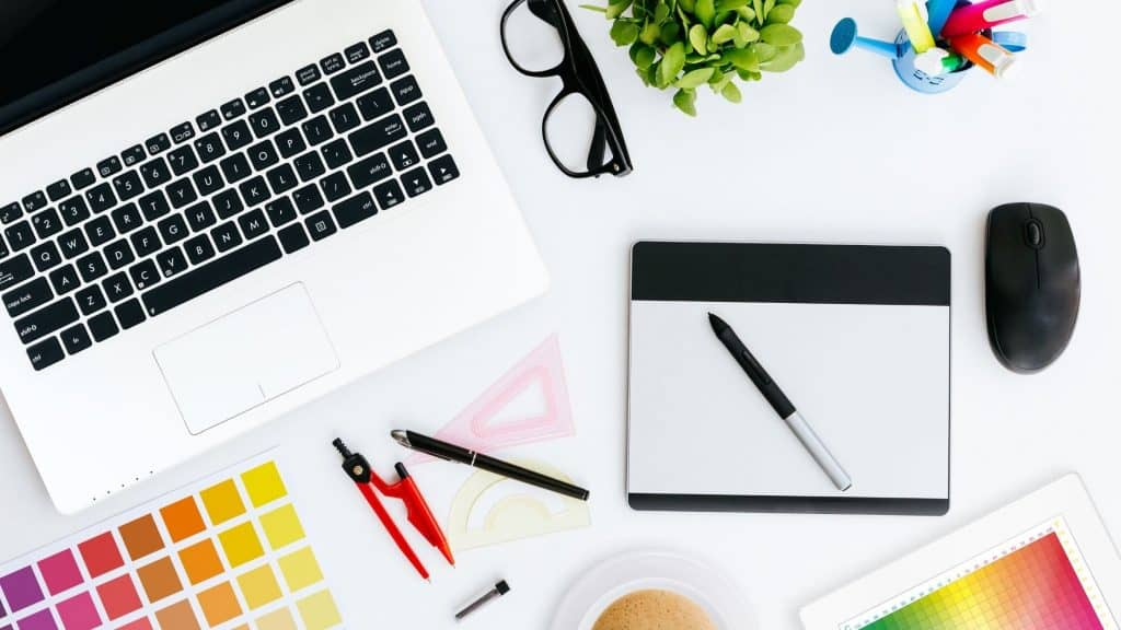 Laptop on desk with graphic design tools.  How to use Canva.