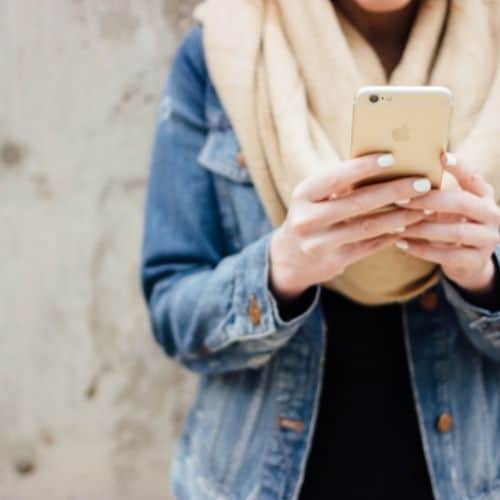 Photo of a girl using an iPhone. How to format a blog post.