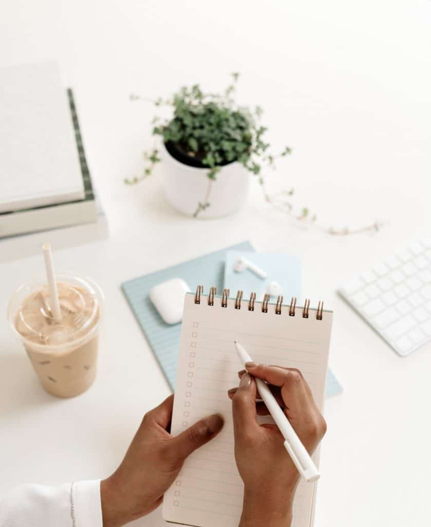 Image of a woman with a notepad and coffee, maybe writing down ideas about how to write her first blog post.