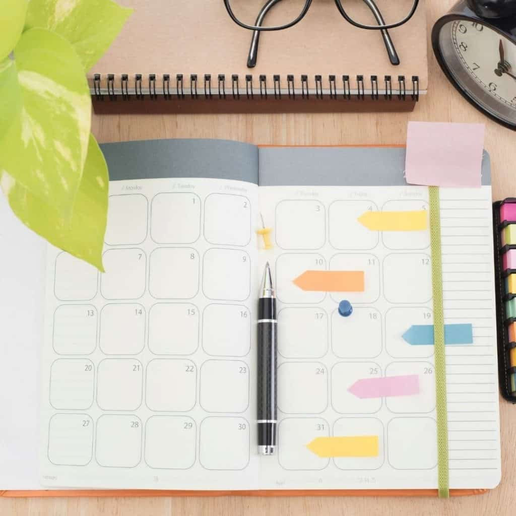Photo of a calendar on a desk with a pen to help beginner bloggers learn to schedule content